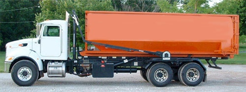 picture of mr dumpster rental truck with orange roll off container parked in Poland
